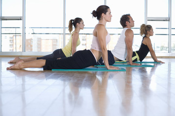 Yoga students in cobra position in class in studio, side view