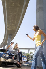 Young woman taking photograph of friends on bonnet of car beneath overpass, low angle view