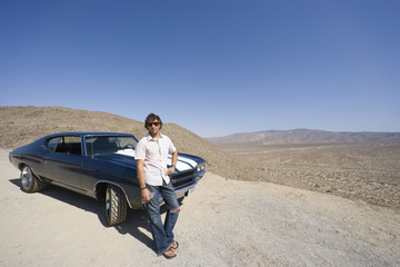 Young man with water bottle in sunglasses by car in desert