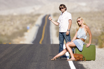 Young couple hitchhiking on desert road, side view