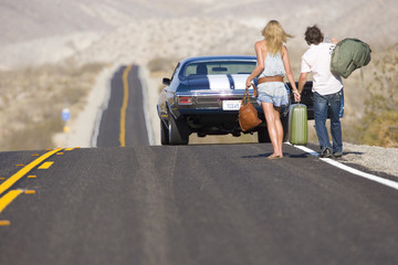 Young couple hitchhiking on desert road, walking towards car, rear view