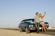 Young couple taking photograph of themselves by car on desert road, low angle view