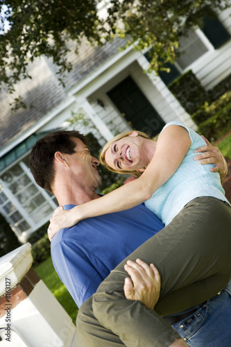 Man carrying his wife across the threshold of their new home