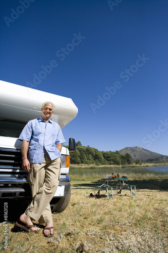 Mature man by motor home and portable picnic table, smiling, portrait, low angle view