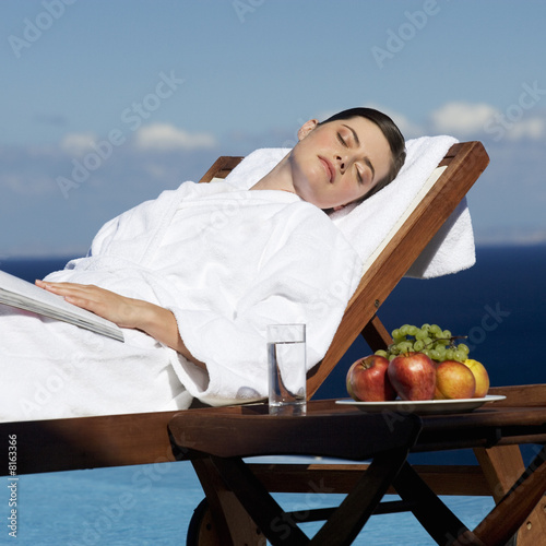 A woman sunbathing by a pool