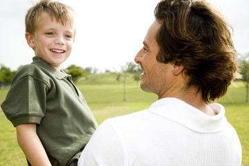 father holding son in the park