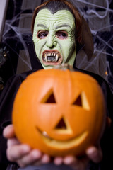 Child in a Count Dracula costume at Hallowe'en, holding a pumpkin with a carved face