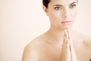 Young woman praying or meditating, hands together