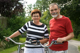 An attractive senior couple bicycling poster
