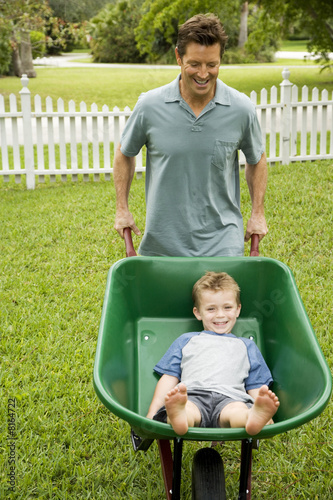 man giving boy a ride in the wheelbarrow