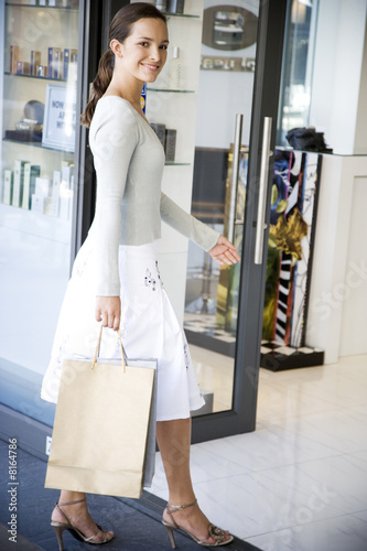 Woman on a shopping trip walking into a store
