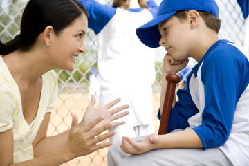 Mother encouraging son at little league baseball game