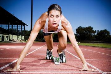 Portrait of female athlete in the starting blocks
