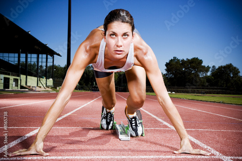 Portrait of female athlete in the starting blocks