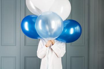 boy hiding behind a bunch of balloons