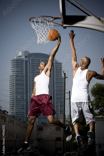 Two Young African American man jumping with a basketball on an urban basketball court