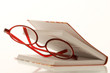red reading glasses between a book