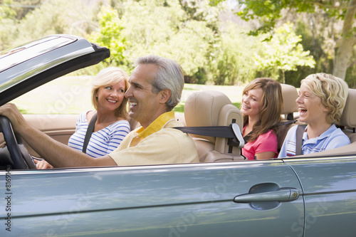 Family in convertible car smiling Poster