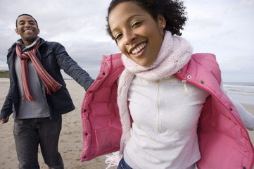 Young couple hand in hand on beach, portrait of woman smiling