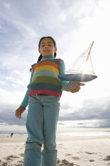Girl (5-7) with toy boat on beach, portrait, low angle view