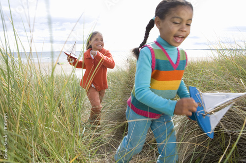 Sisters (5-9) with toy boats on sand dune (blurred motion)