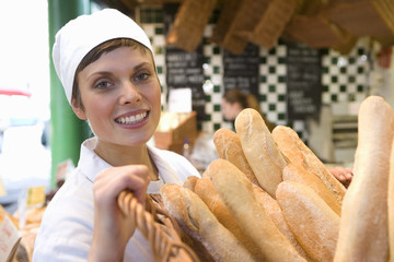 Female baker with basket of baguettes in bakery, smiling, portrait