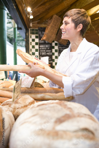 Female baker with baguettes in bakery, smiling, side view