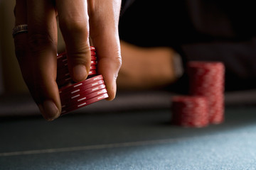 Woman placing gambling chips on table, close-up