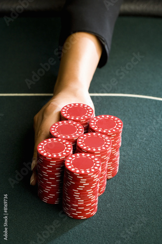 Woman pushing gambling chips onto table, close-up of hand