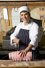 Female butcher at work, smiling, portrait