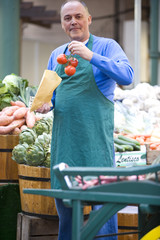 Green grocer putting tomatoes in bag, smiling, portrait
