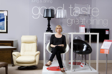 Shop assistant on chair in furniture shop, portrait