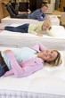 Family of three testing beds in furniture shop, smiling, portrait