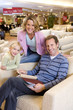 Family of three in furniture shop, man in armchair, smiling, portrait