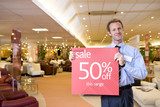 Salesman with 'sale' sign in furniture shop, smiling, portrait