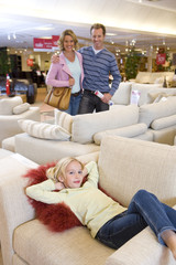 Family of three in furniture shop, girl (6-8) on sofa, smiling, portrait