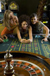Young woman collecting pile of gambling chips from roulette table, flanked by friends, smiling