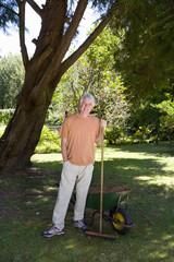 Senior man with rake by wheelbarrow, smiling, portrait
