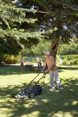 Senior man mowing lawn, wife and granddaughter with wheelbarrow in background
