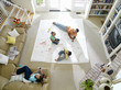 Family of four in living room, drawing on large piece of paper on floor, elevated view