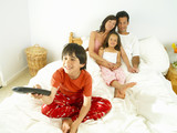 Family of four in bed, boy (8-10) with remote control, smiling