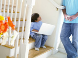 Boy (5-7) with laptop on stairs, looking at father