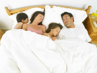 Family of four asleep in bed, elevated view