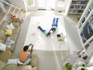 Family of four in living room, mother, son and daughter (6-10) drawing on large piece of paper on floor, elevated view