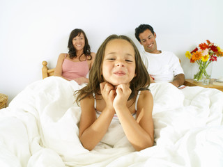 Girl (5-7) in bed with parents, smiling, portrait