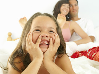 Girl (5-7) in bed with parents, smiling, close-up