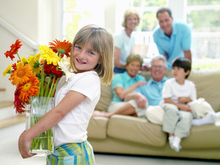 Girl (6-8) with vase of flowers, family on sofa in background, smiling, portrait