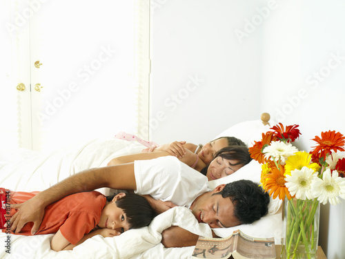 Family of four asleep in bed, portrait of boy (8-10) smiling