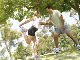 Young couple stretching in preparation for running, smiling at each other (tilt)