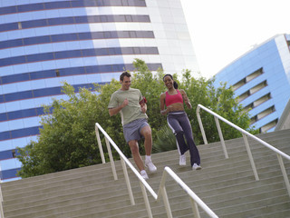 Man and woman running down stairs, low angle view